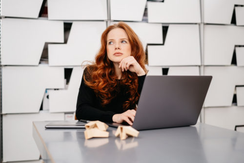 Pretty redhead woman sitting daydreaming at work with an open laptop in front of her in a modern office