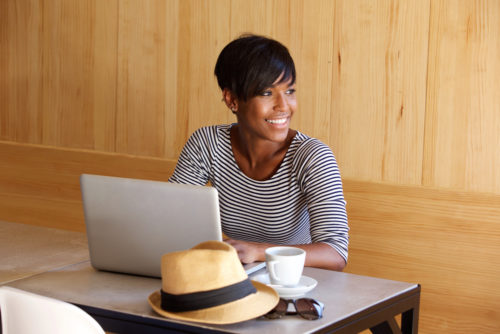 Portrait of a young black woman smiling and using laptop