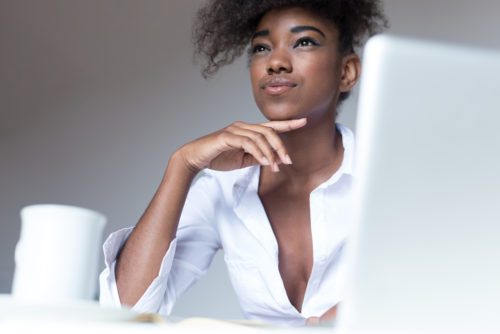 Stylish dark-skinned woman food blogger with curly haircut publishing new posts on social networks, using laptop