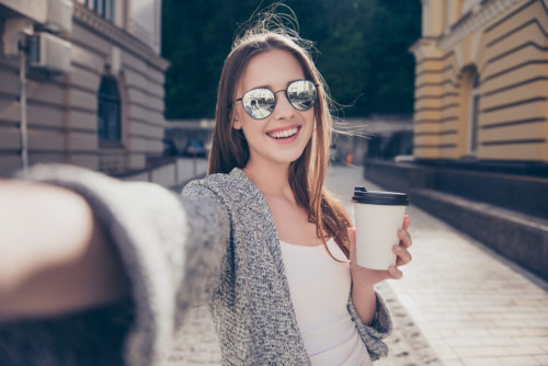 Cheert! Selfie time! Young happy lady in a spring vacation, walking in the city, drinking coffee, photographing herself on a sunny day