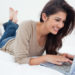 A smiling woman lying down the bed in front of her laptop with her legs raised slightly