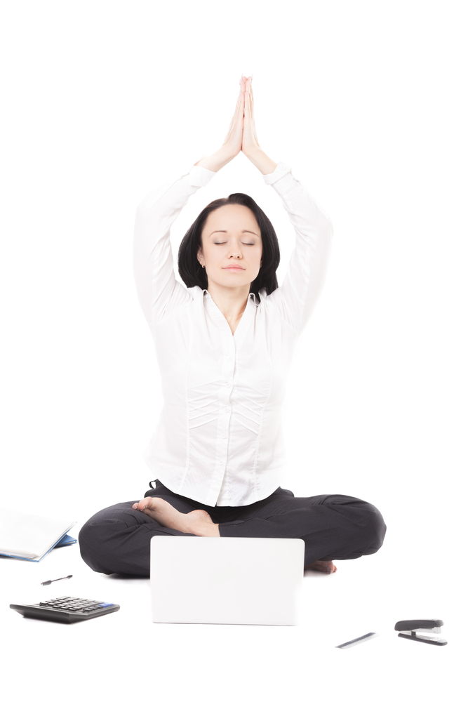 Business, study, healthy lifestyle, work at home. Serene young female professional surrounded by office accessories meditating in yoga Padmasana (Lotus Pose) in front of laptop, isolated